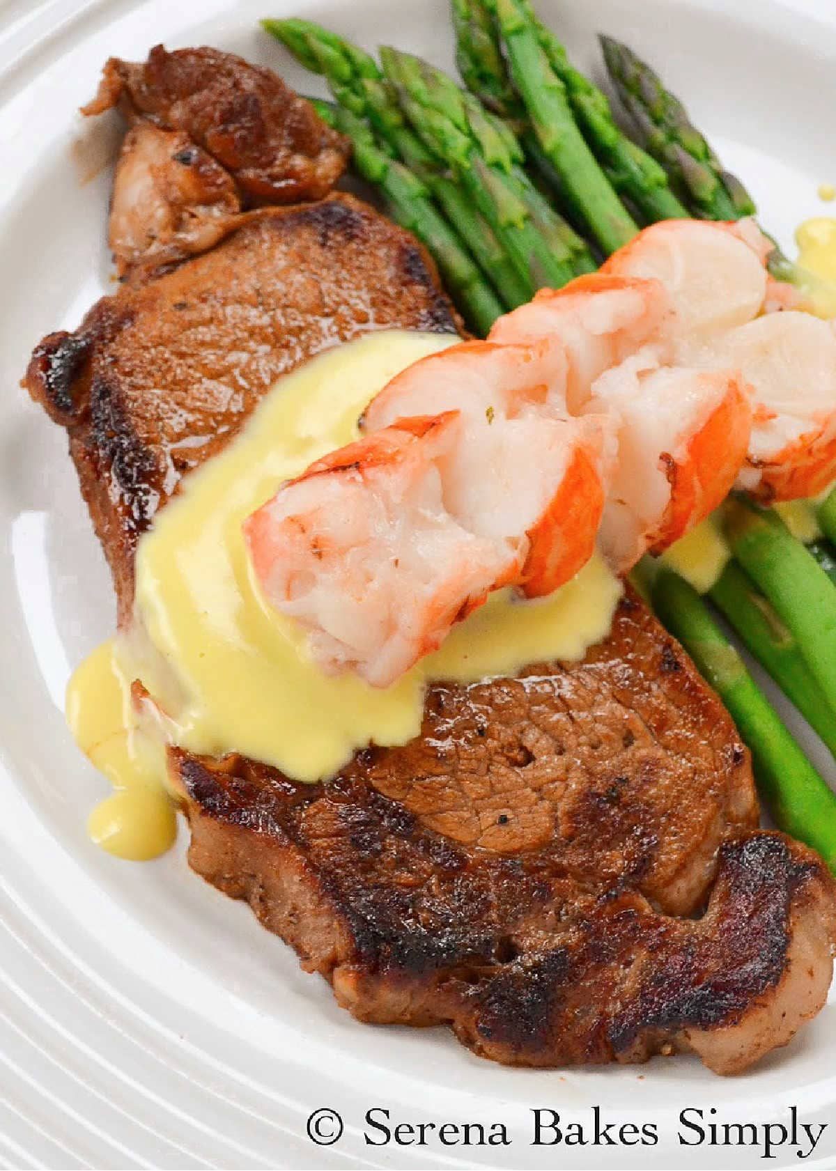 Pan Seared Steak on a white plate covered with Hollandaise Sauce and Sliced Lobster Tail with Asparagus on the side for Fathers Day.