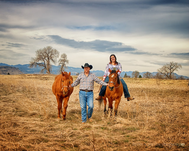engagement photo of a couple and two horses in colorado