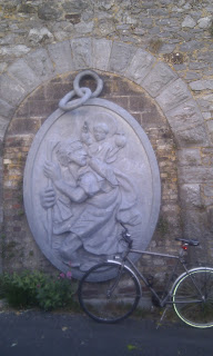 A sculpture of a medallion of St Christopher on NCN 27 (Devon Coast to Coast route)