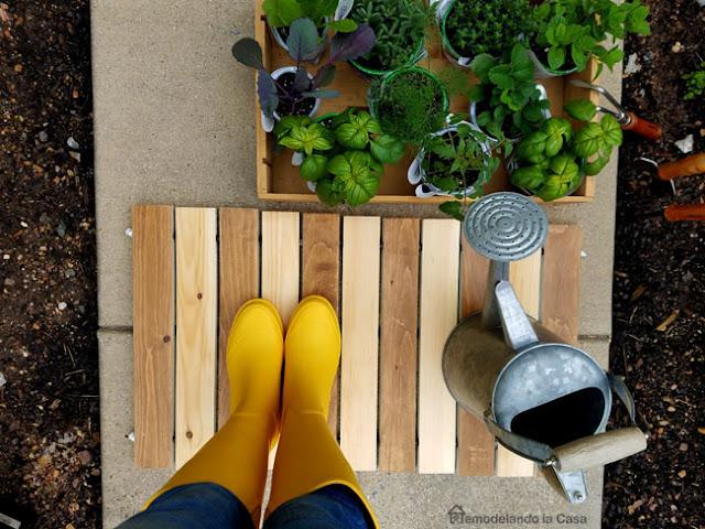 garden, herbs, stained planks door mat, yellow rain boots, watering can, dirt, garden tools