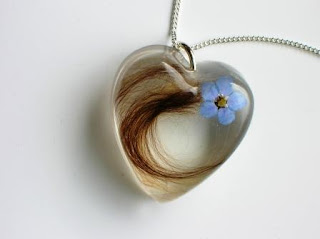 A lock of hair and forget me not flower pendant