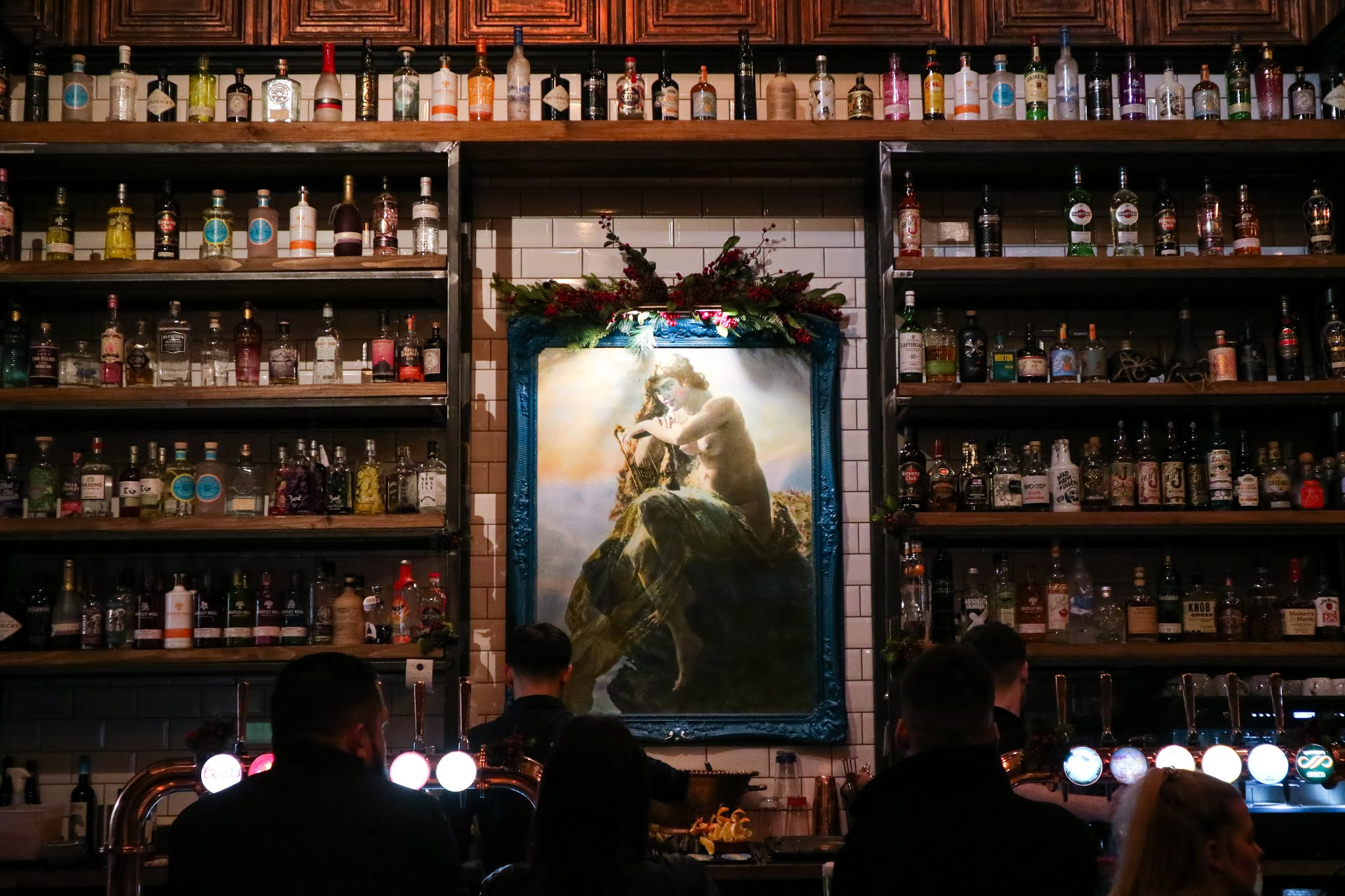 The bar at The Ship's Cat North Shields with a beautiful Venus mural and shelves of liquor bottles