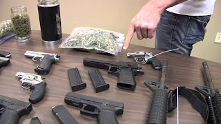 Drugs and guns on table with man pointing at them.