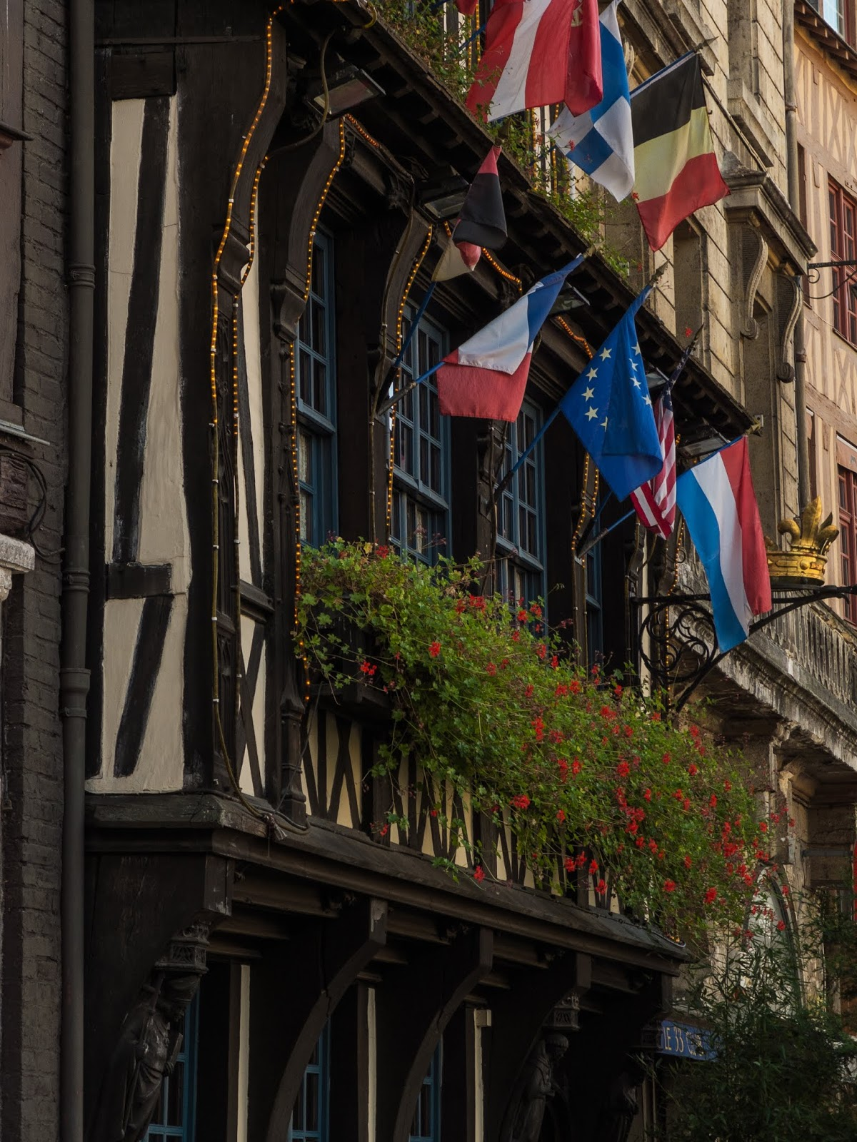 Front of a building with flags and flowers on Place du Vieux Marche in Rouen, France.