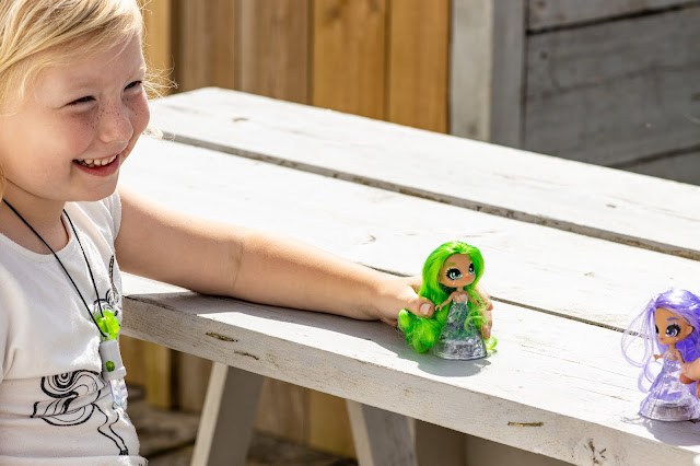 A happy 5 year old holding a Crystalina doll and wearing the green amulet and smiling