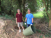 two men in work clothes collecting weeds in can