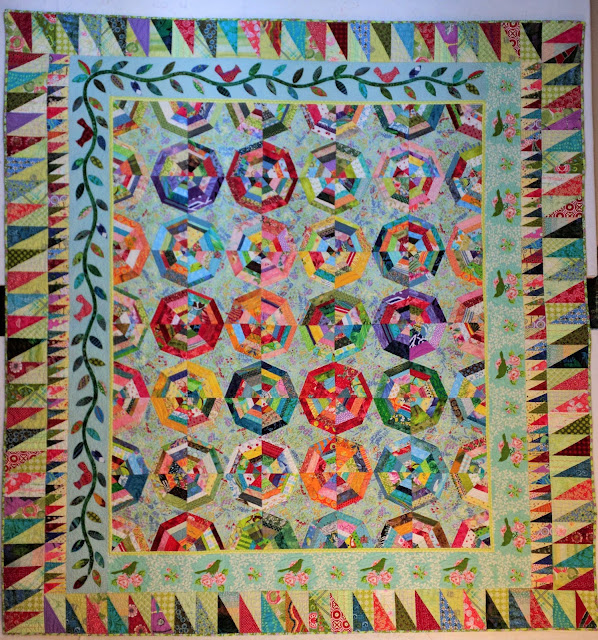 The spiderwebs in the center of the quilt are outlined in various single colors including red, green, blue, yellow, and purples. There is a narrow light green inner border followed by a border that is a printed toile on two sides and an applique vine on the other two. Finally there are two more borders of improvisational right triangles as the outer border.