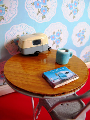 Modern dolls' house miniature scene of a retro table and chair. On the table is a model caravan, a mug of coffee and a book on retro caravans.