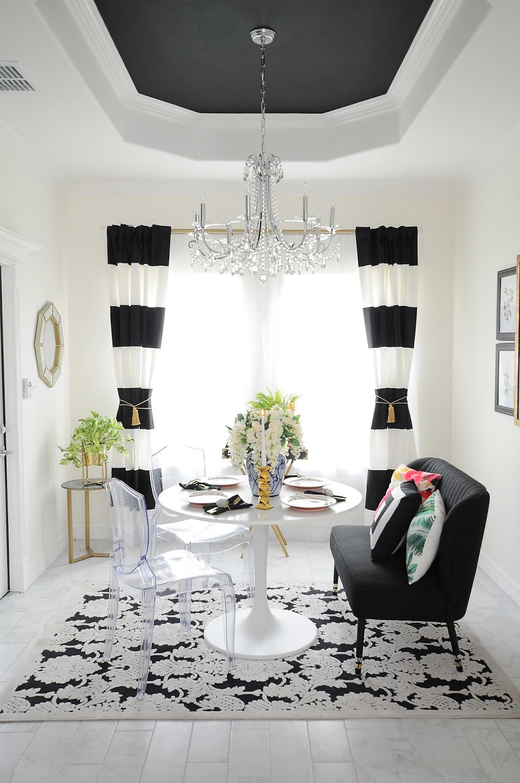 Black and white striped curtains frame a small dining room space with audubon, floral and botanical decor accents.