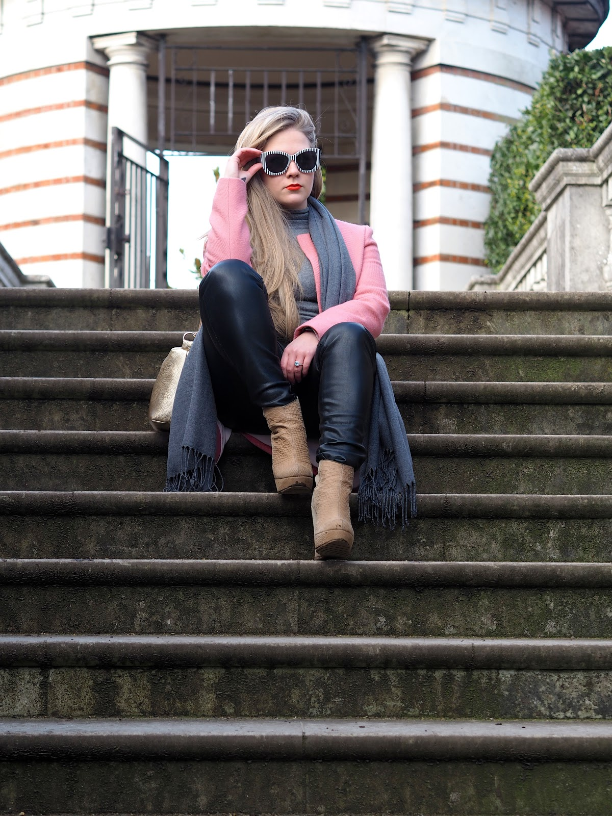Blonde girl wearing sunglasses and pink coat sitting on grey steps