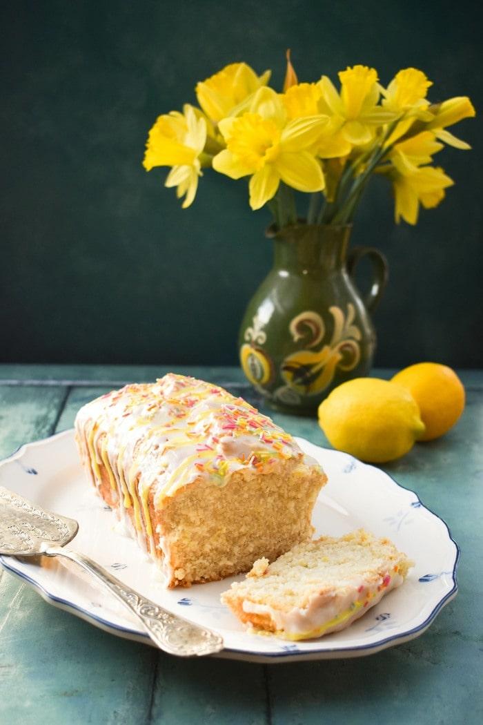 Vegan lemon cake on a white platter next to a vase of daffodils