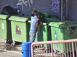 A hungry man looking for food in a large dustbin.