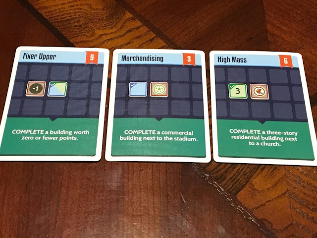 Three contract cards in the Expancity board game by Breaking Games, photo by Benjamin Kocher