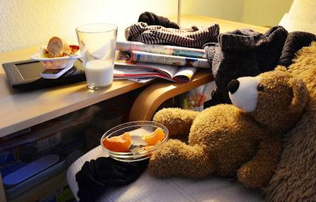 """Hiukan sekaaisessa ympäristössä """"nalle"""" lojuu sohvalla ja syö siinä ateriaansa... kovasti """"kotoisen oloisesti""""."""
