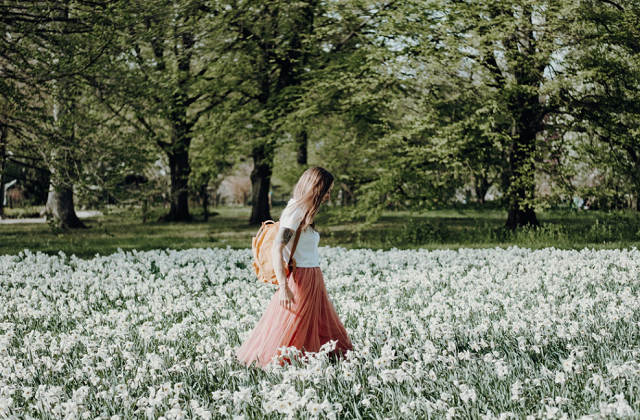 woman white shirt pink long dress walking in the field of white flowers