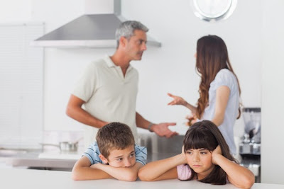 Unhappy siblings sitting in kitchen with their parents who are fighting at home loudly
