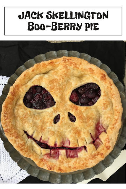 A finished Jack Skellington boo berry pie on a pie plate and stand.