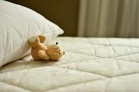 a small teddy lying on a mattress