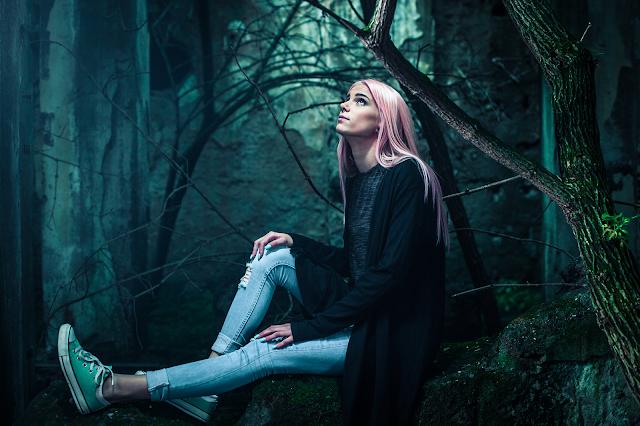 Giovane donna assorta nei suoi pensieri, in un bosco.