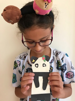 Child holding their panda craft