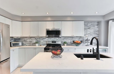 Modern kitchen with white cabinets and matte black sink.