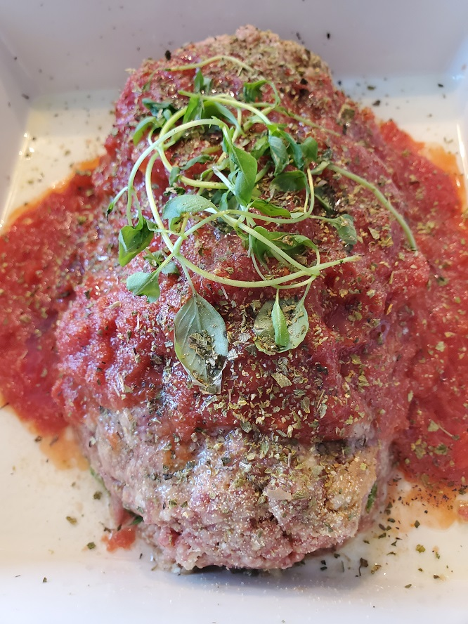 this is raw ground beef mixed into a meatloaf with marinara sauce on top