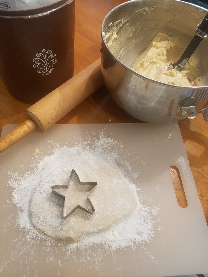 This is sugar cookie dough with a rolling pin, mixing bowl, flour on a cutting board ready to make cookies with
