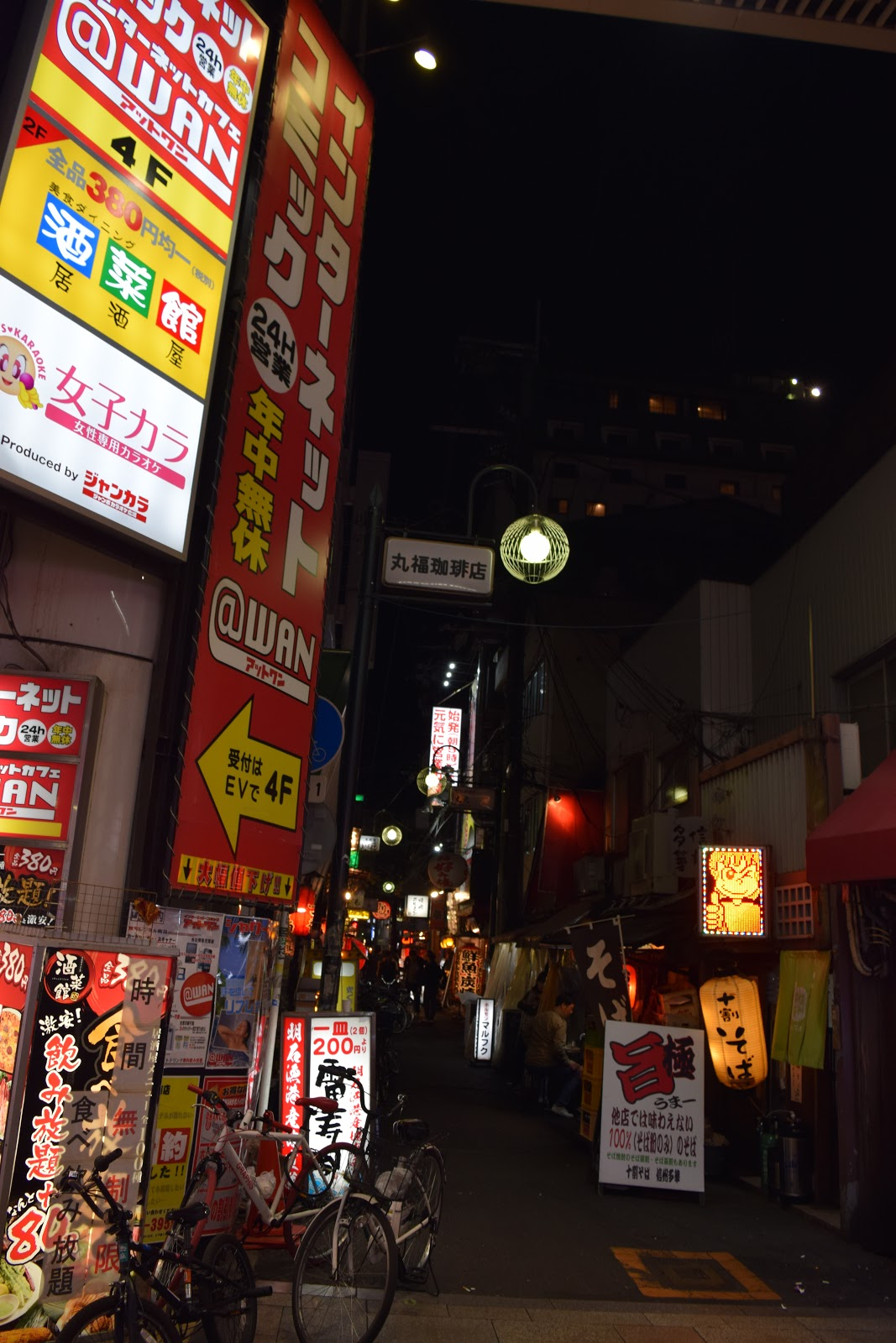 internet cafe sign and side street in namba, osaka at night