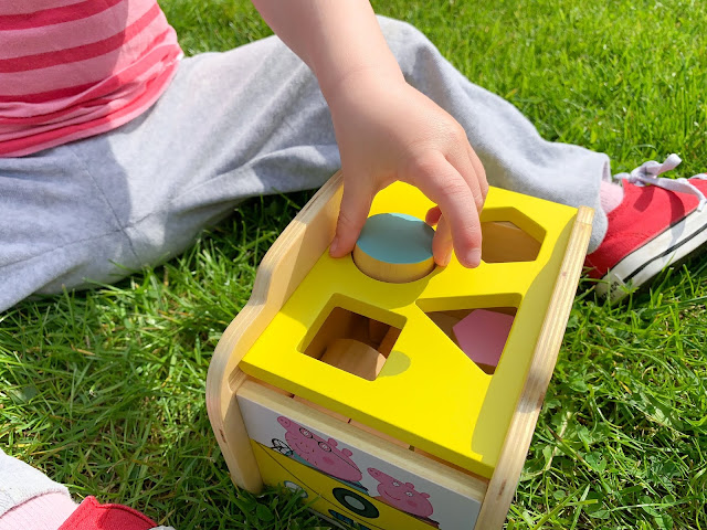 Close up of toddler putting a block into shape sorter