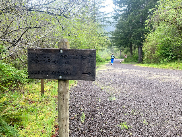 Trail sign for Jones Creek campground with Ann in the background