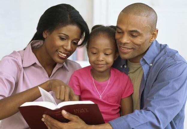 Padres enseñando Biblia a su hija
