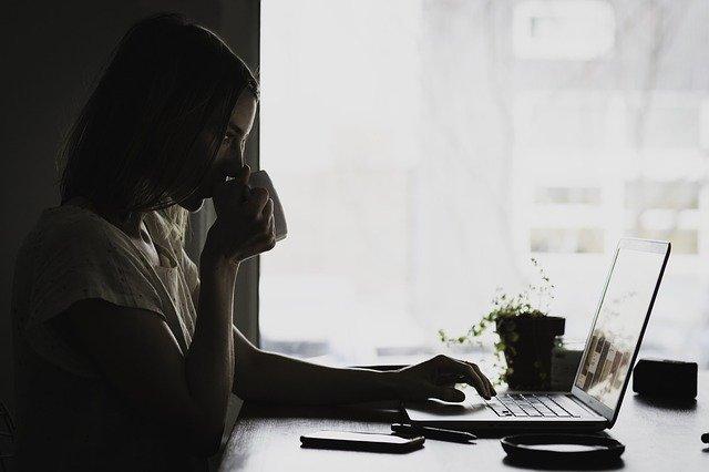 wanita tengah menghirup kopi didepan laptop