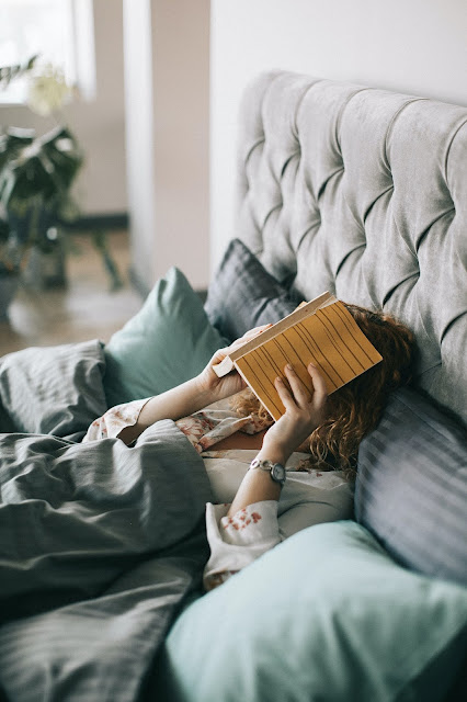 https://www.pexels.com/photo/woman-covering-face-with-book-on-bed-1524232/