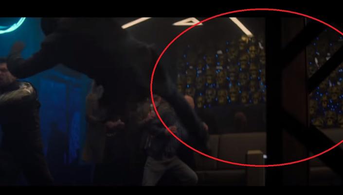 Imagem: Cena do interior de uma sala, várias pessoas estão brigando e uma delas empurrou um homem que está sendo arremessado no ar. No fundo da imagem circulado em vermelho destacado da imagem tem uma parede cheia de caveiras de Skrulls que são cabeças meio com textura de réptil e na cor verde.