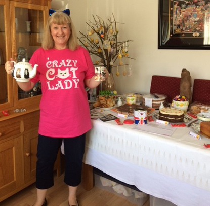 woman in crazy cat lady tshirt with cake sale spread