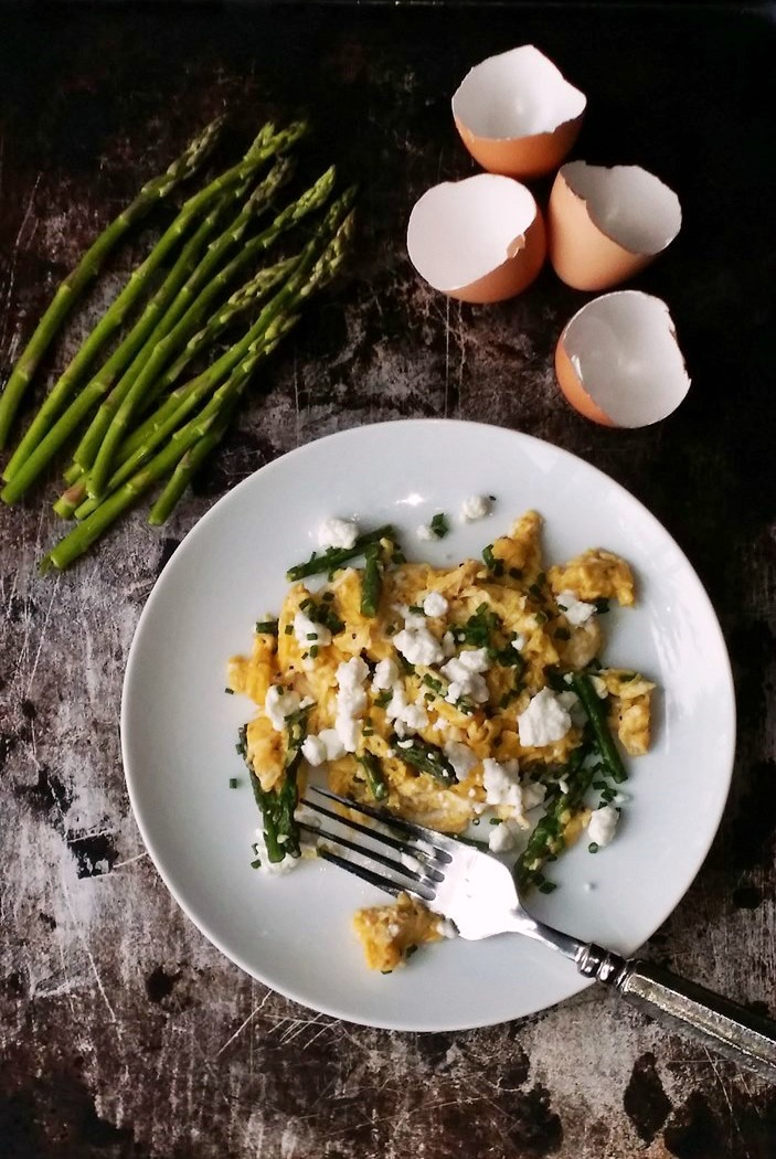 Overhead photo of Perfectly Scrambled Eggs with Asparagus and Goat Cheese on a white plate with a metal background.