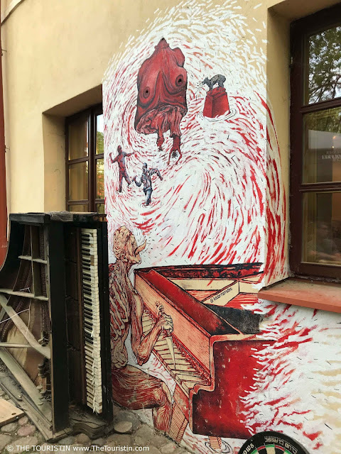Red and white mural by Indian street artist Kedar Namdas Užupis