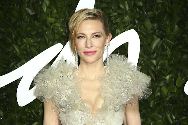 A imagem mostra a atriz Cate Blanchett posando para a câmera. Ela é caucasiana, loira e usa um vestido bege com plumas. Ela está sorrindo.