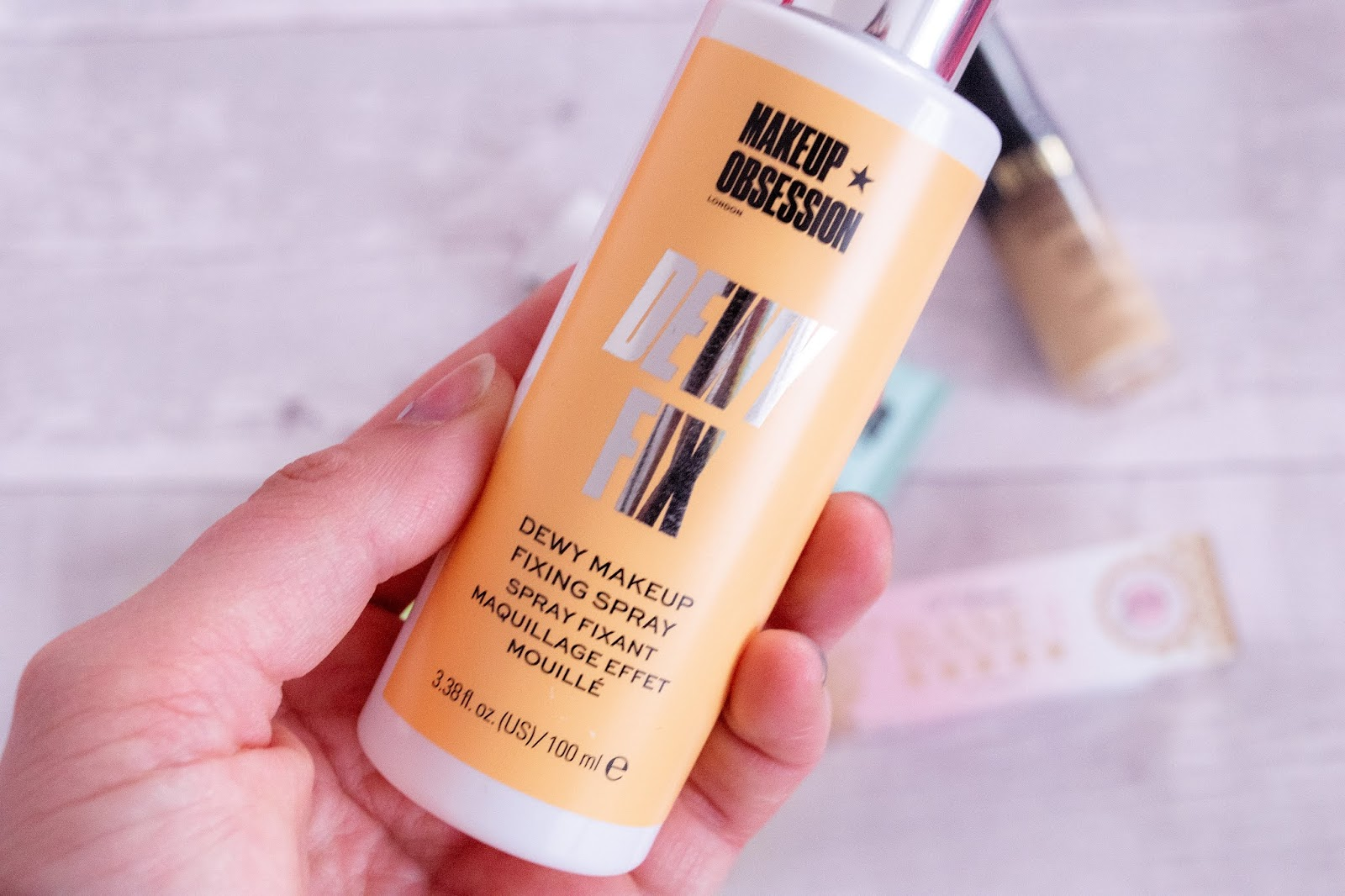 A close up of the Makeup Obsessions Dewy Finish Fixing Spray. The bottle is white with a spray top and an orange label.