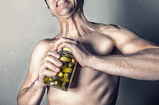 A topless white man struggles to open a jar of pickled gherkins.