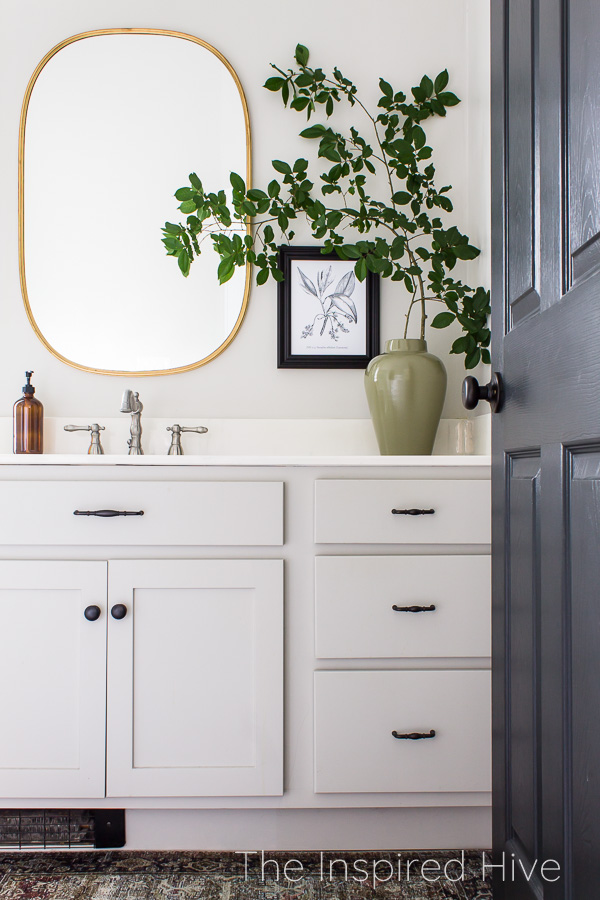 Master bathroom with greige vanity cabinets, oil rubbed bronze hardware, nickel faucet, and brass mirror. Large green vase with oversized greenery.