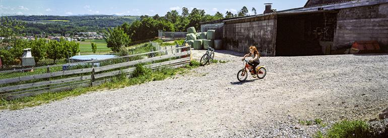 Une cour de ferme en Suisse avec une fillette à vélo.