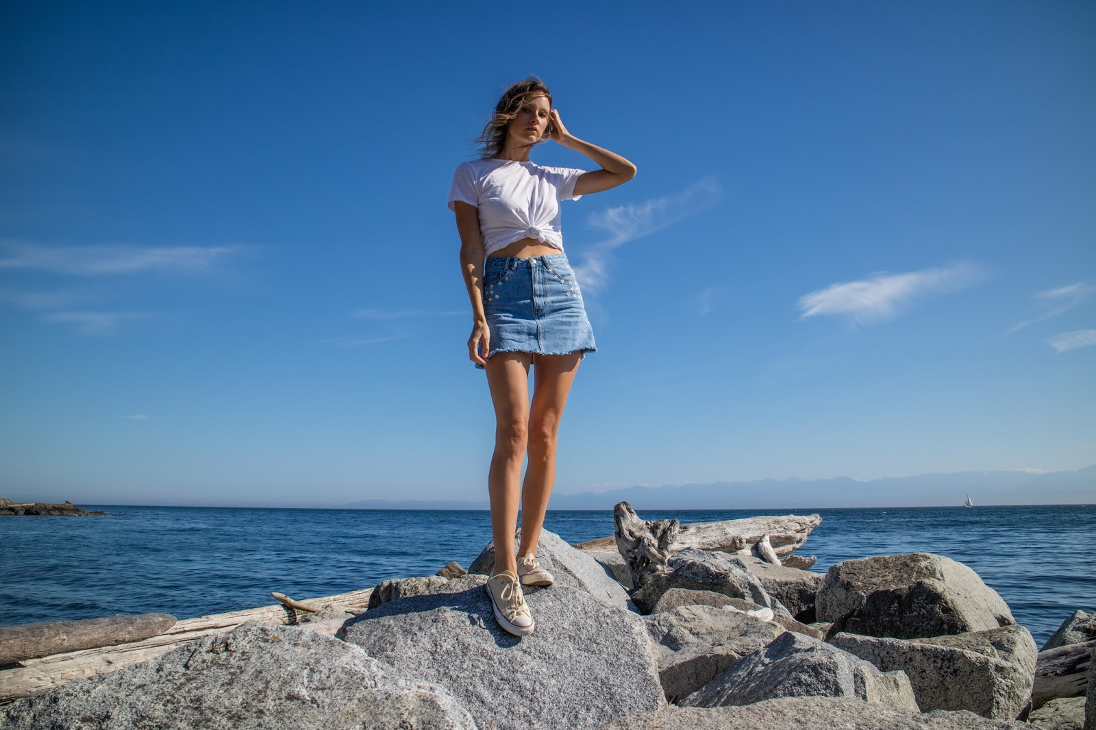 fashion blogger, Alison Hutchinson, is wearing a casual summer look in a white tee and denim skirt by Insight