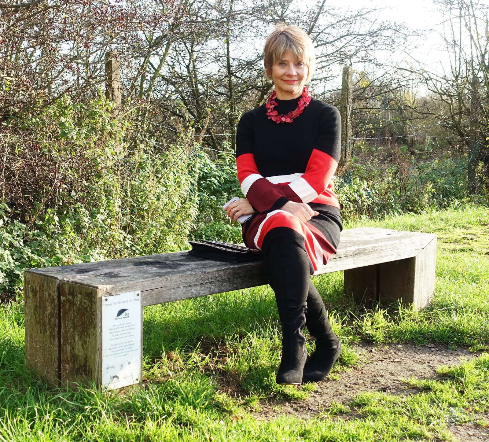 Image showing woman over 50 seated on a bench overlooking a canal wearing a colour block wool two piece outfit and over the knee boots