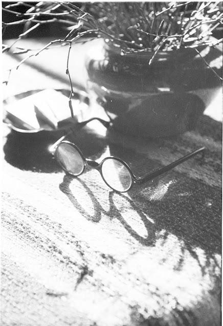 Mustavalkoinen kuva. Kuvassa pöydällä maljakko ja sen vieressä mustat paksusankaiset silmälasit.
