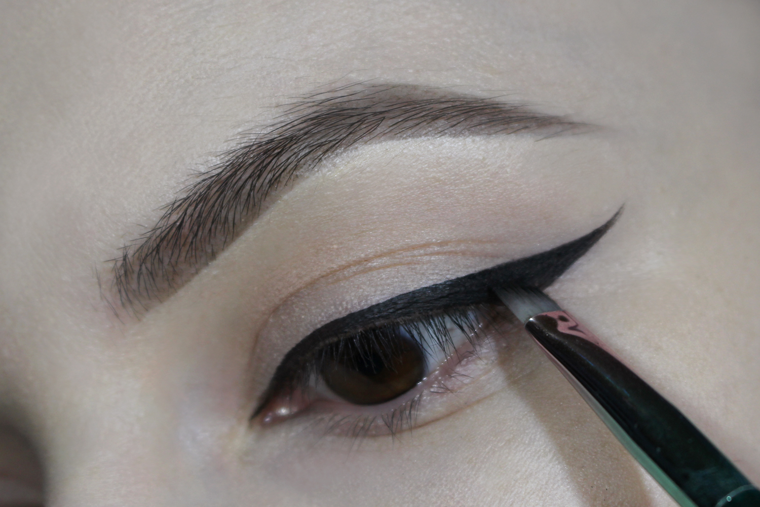 a close-up picture of an eye with a black cat eyeliner makeup look