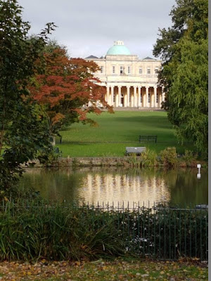 Building with colonnade and dome viewed through trees and reflected in a lake