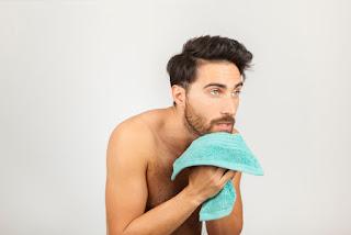 homem secando rosto com toalha