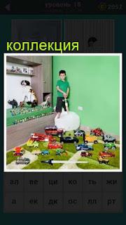 мальчик в комнате а вокруг него большая коллекция игрушек на полу и полках