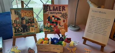 Na sztalugach dwie książki o motylach oraz napis Dzień motyla. Pod sztalugami motyle i kwiaty w wiklinowym koszyku. spodem na
